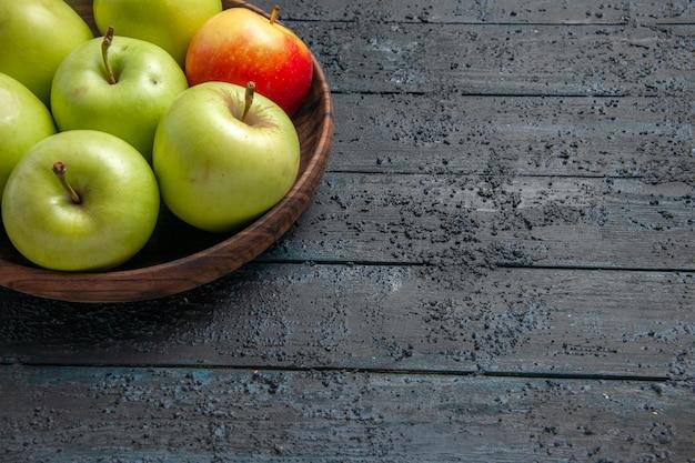 Widok z boku jabłka w misce miska zielono-czerwono-żółtych jabłek po lewej stronie drewnianego stołu