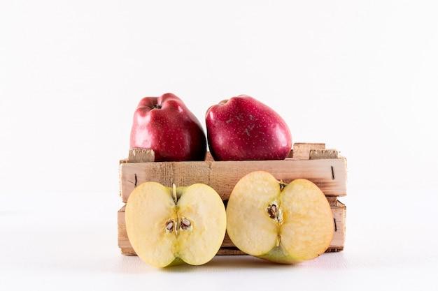 Widok z boku jabłka w połowie pokrojone w skrzynie