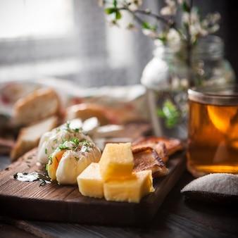 Widok z boku jajko sadzone z filiżanką herbaty i sera oraz kwiaty w słoiku w naczyniach na pokładzie