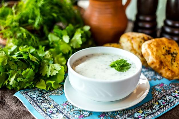 Widok z boku jogurt zupowy dovga z ziołami ryż i chleb na stole