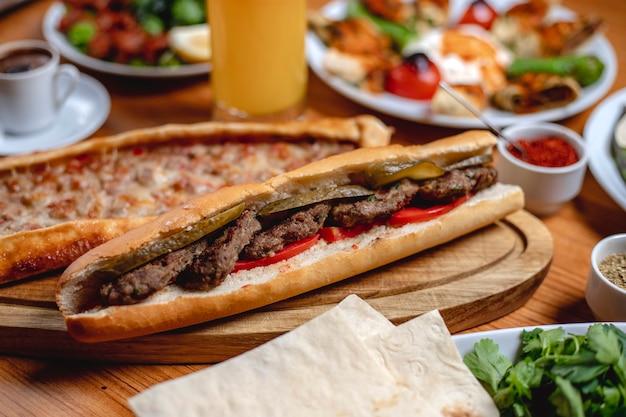 Widok z boku kanapka biały chleb z kotletami mięsnymi, świeżym pomidorem i kiszonym ogórkiem na desce