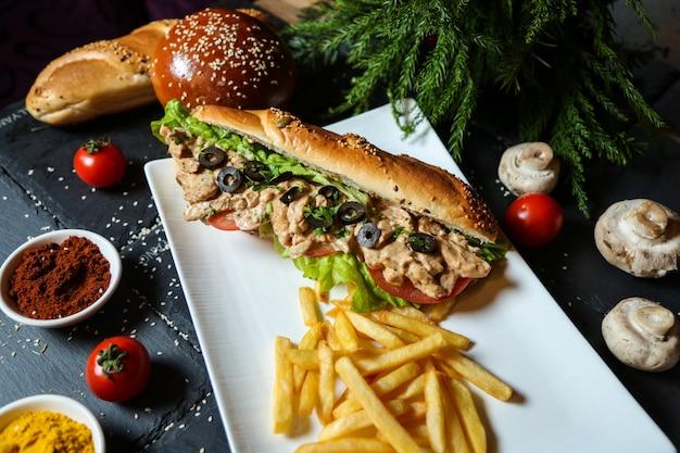 Widok z boku kanapka z kurczakiem w chlebie z frytkami, pomidorami i grzybami z przyprawami