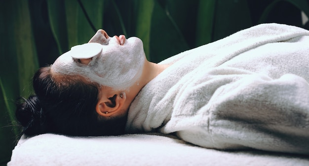 Widok z boku kaukaskiej damy leżącej w salonie spa z białą maską na twarzy i dyskami na oczach