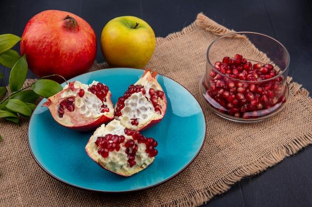 Widok z boku kawałków granatu na talerzu z jagodami w całości i jabłkiem z liśćmi na worze i czarnym