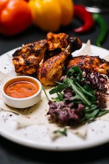 Widok z boku kebab z kurczaka na lawaszu ze świeżą ziołową cebulą i sosem adjika