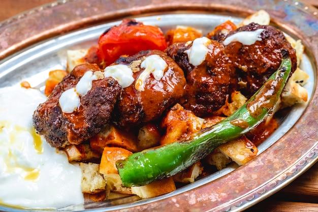 Widok z boku kebab z rusztu z grilla, kotlety mięsne z sosem pomidorowym z gorącym zielonym pieprzem i jogurtem na chlebie