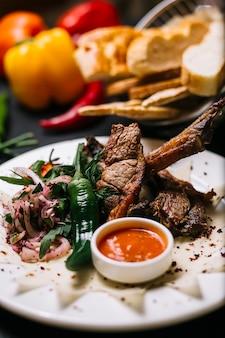 Widok z boku kebab żeberka jagnięce z zielonymi ziołami papryczki chili i pikantnym sosem na białym talerzu