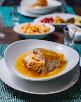 Widok z boku khash z marynowanym ogórkiem wiśniowym bakłażanem czereśniowym śliwkowym octem czosnkowym i bułeczką na stole