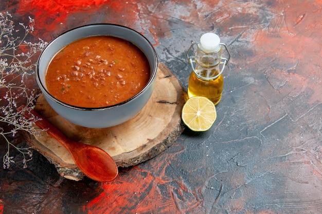 Widok z boku klasycznej zupy pomidorowej w niebieskiej misce na drewnianej tacy butelce oleju i cytryny na stole mieszanym