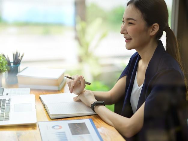 Widok z boku kobiecego wykonawczej elegancji, która ma spotkanie konferencyjne online