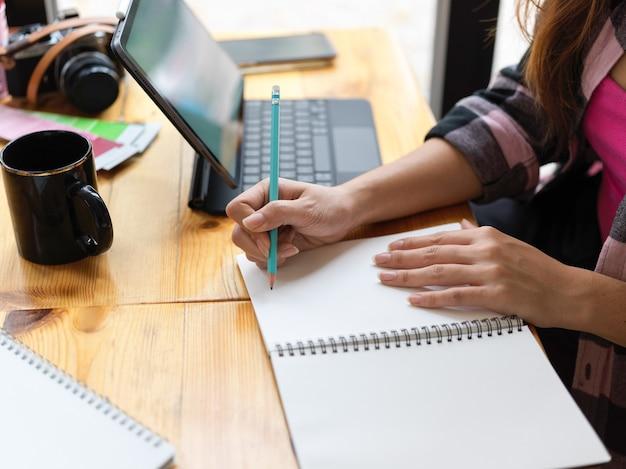 Widok z boku kobiecej dłoni nastolatka pisania na pustym notatniku podczas nauki online za pomocą cyfrowego tabletu