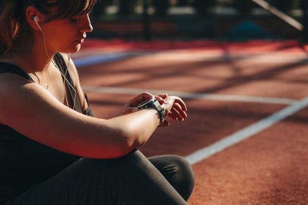 Widok z boku kobiecej dłoni patrząc na jej zegarek sportowy przed wykonaniem ćwiczeń schudnąć rano w parku sportowym.