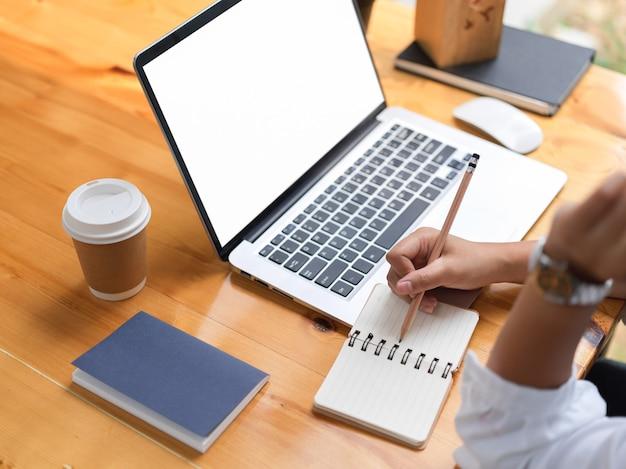 Widok z boku kobiecej dłoni pisania na pustym notatniku podczas pracy z laptopem na ścieżce przycinającej drewniany stół
