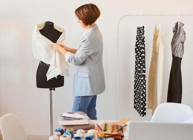 Widok z boku kobiecej projektantki mody w atelier z ubioru