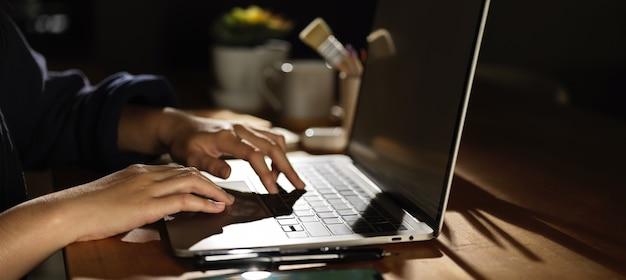 Widok z boku kobiecej ręki pisania na laptopie na drewnianym stole z dostawami i dekoracjami