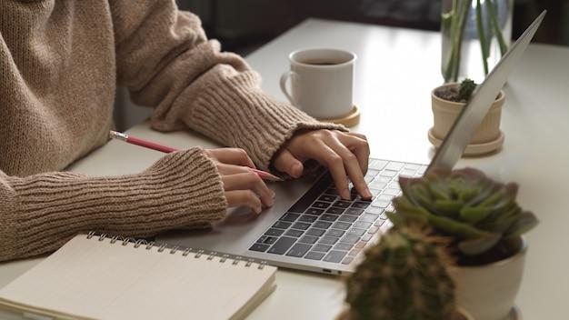 Widok z boku kobiecych rąk pisania na klawiaturze laptopa