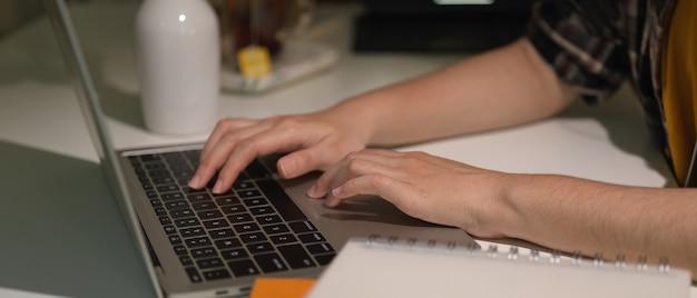 Widok z boku kobiecych rąk, wpisując na klawiaturze laptopa na białym stole w pokoju biurowym