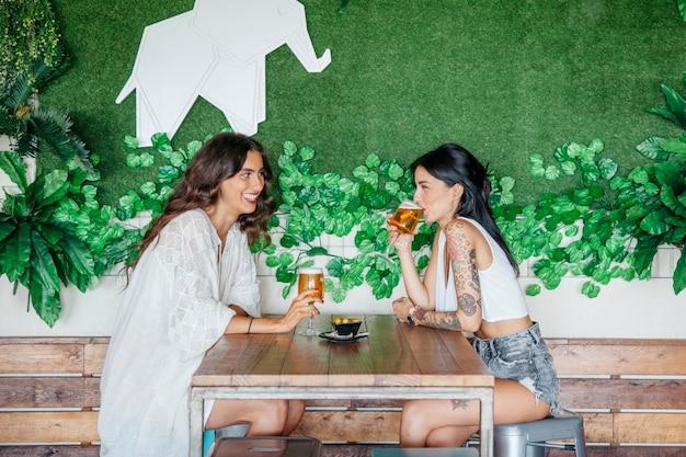 Widok z boku kobiet pijących piwo przy stole