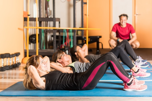 Widok z boku kobiet robi ćwiczenia abs w siłowni. koncepcja siłowni.