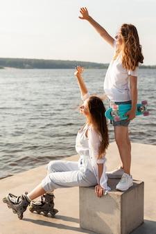 Widok z boku kobiet z rolkami i deskorolką nad jeziorem