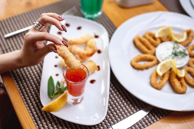 Widok z boku kobieta je krewetki w cieście ze słodkim sosem chili i plasterkiem cytryny