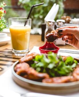 Widok z boku kobieta je smażonego kurczaka w cieście z sosem ziołowym i sokiem pomarańczowym