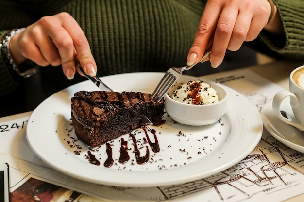 Widok z boku kobieta jedzenie ciasto czekoladowe z lodami i polewą czekoladową na talerzu