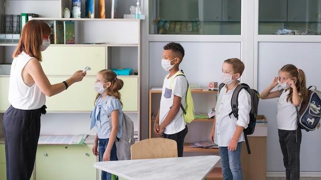 Widok z boku kobieta mierząca temperaturę dzieci
