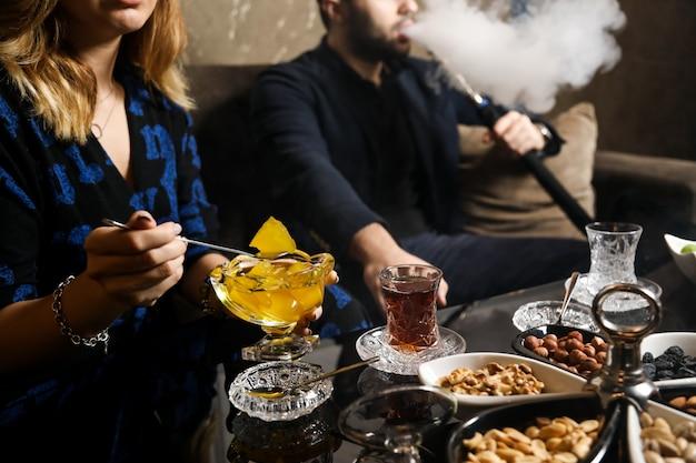 Widok z boku kobieta nakłada dżem ananasowy na spodek z orzechami i szklanką herbaty na stole