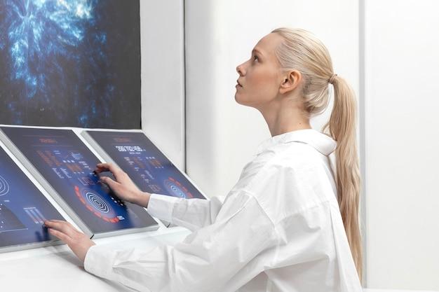 Widok z boku kobieta pracująca na monitorach cyfrowych
