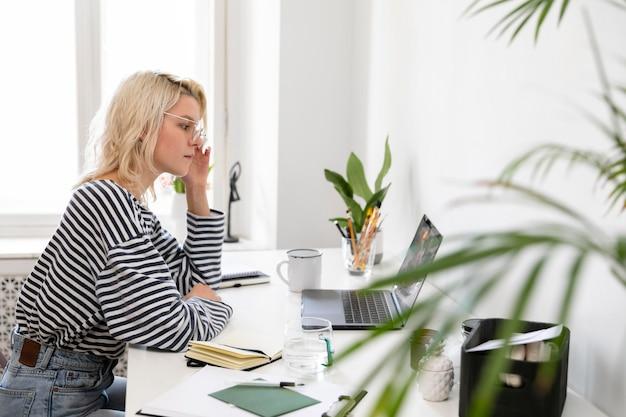 Widok z boku kobieta pracująca w domu