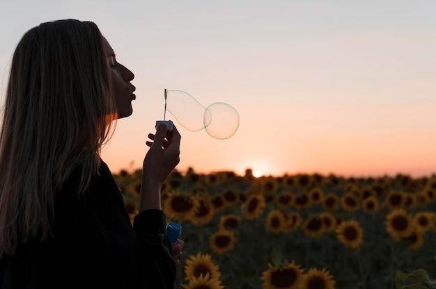 Widok z boku kobieta robi balony mydlane