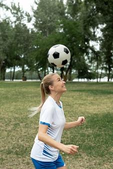Widok z boku kobieta rzuca piłkę