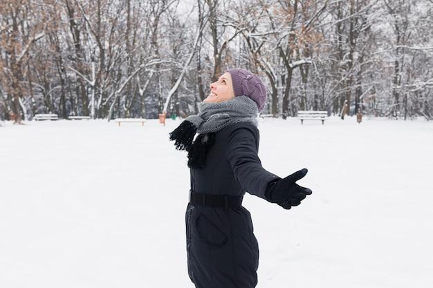 Widok z boku kobieta ubrana w ciepłą odzież korzystających zimowy dzień