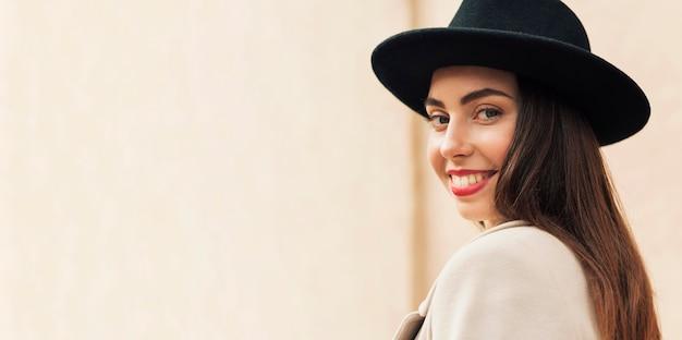 Widok z boku kobieta ubrana w czarny kapelusz z miejsca na kopię