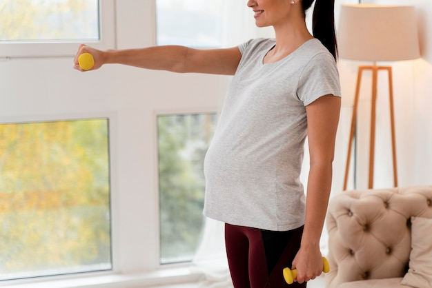 Widok z boku kobieta w ciąży szkolenia z ciężarami