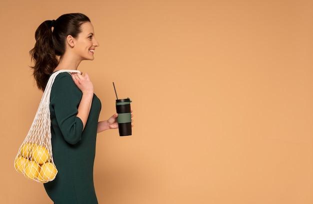 Widok z boku kobieta w ubranie niosące torbę wielokrotnego użytku żółwia