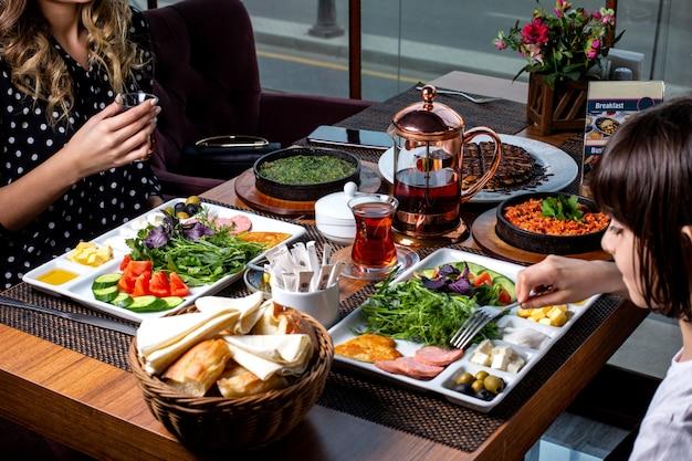 Widok z boku kobieta z dzieckiem jedząca śniadanie serwowany stół jajecznica z ziołami z przystawkami warzywa naleśniki chleb i herbata