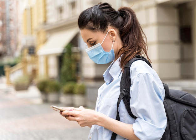 Widok z boku kobieta z maską medyczną sprawdzanie swojego telefonu