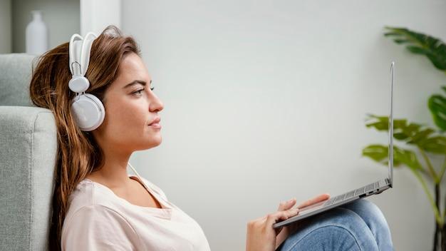 Widok z boku kobieta ze słuchawkami za pomocą laptopa