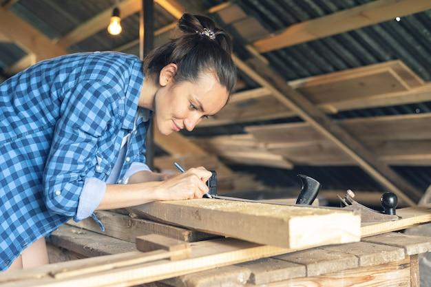 Widok z boku kobiety cieśli rysuje na drewnianej linii cięcia deski