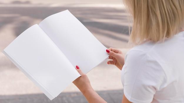 Widok z boku kobiety czytającej książkę na zewnątrz