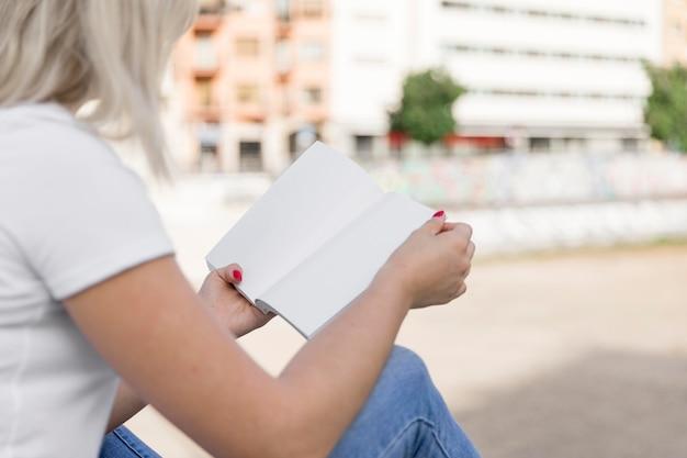 Widok z boku kobiety czytanie książki na zewnątrz