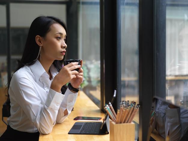 Widok z boku kobiety freelancer pije kawę patrząc przez szklane okno