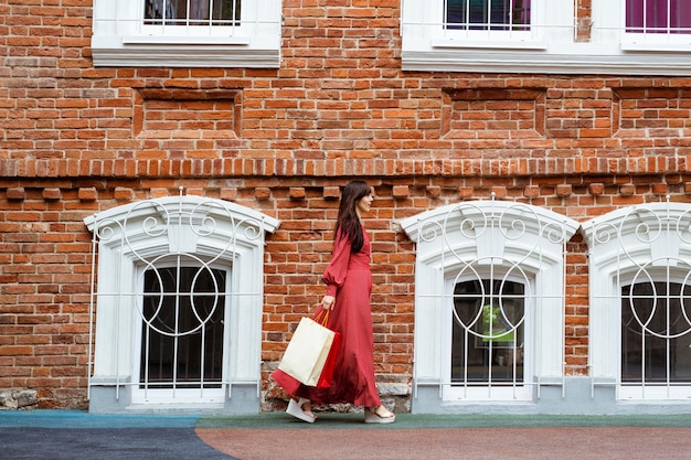 Widok z boku kobiety idącej ulicą z torby na zakupy