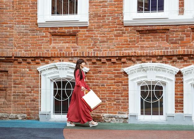 Widok z boku kobiety idącej z torby na zakupy