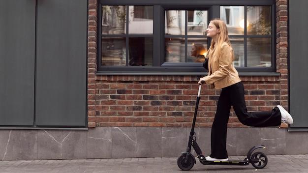 Widok z boku kobiety jadącej skuterem elektrycznym na zewnątrz z miejsca na kopię