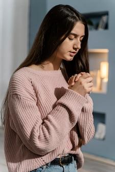 Widok z boku kobiety modlącej się w domu