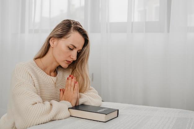 Widok z boku kobiety modlącej się z biblii w domu i przestrzeni kopii