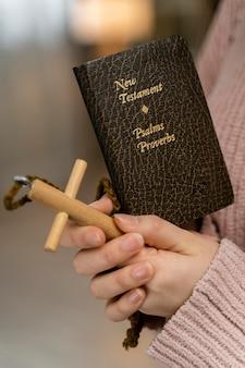 Widok z boku kobiety modlącej się z drewnianym krzyżem i biblią